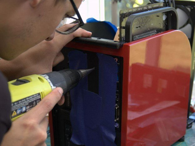 Image of Josiah Fast working on Spirit of Motion drilling a hole for the power button