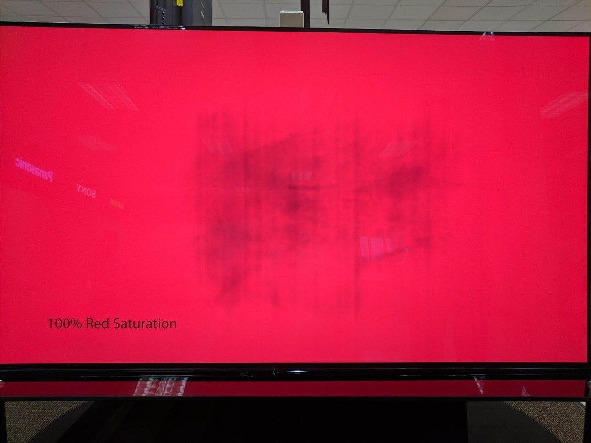 An OLED monitor with a red background showing a burn-in effect near the centre