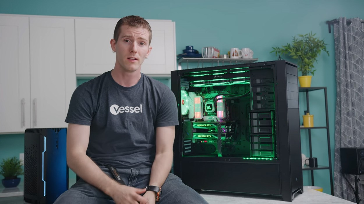 Linus Sebastian of Linus Tech Tips sat on a desk next to a PC inside an E-ATX case.